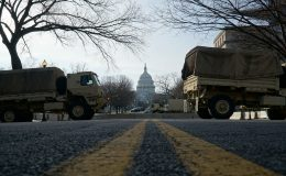 Military trucks passing the US Capital in the background